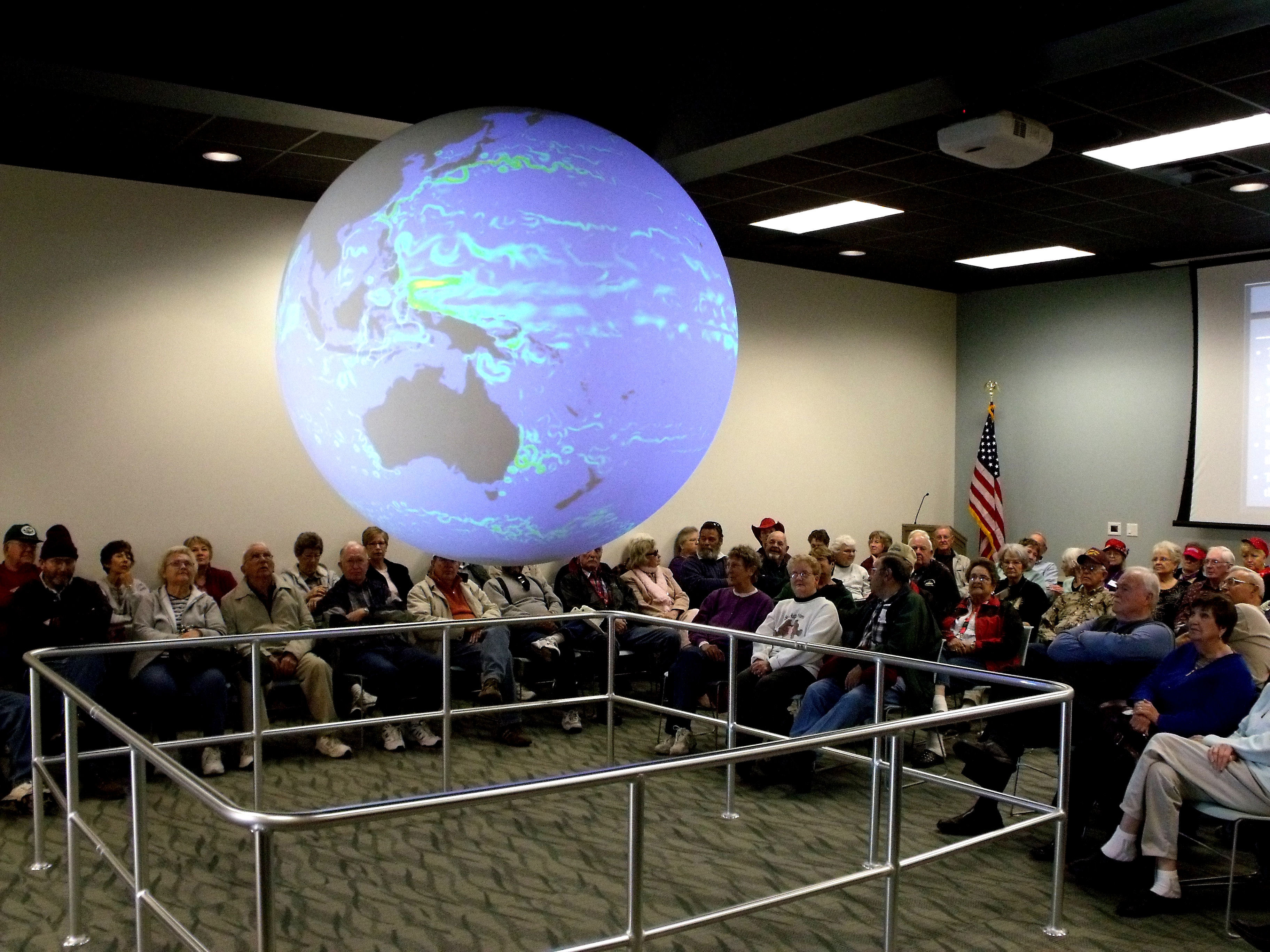 Visitors attend a Science on a Sphere presentation at the Bay Education Center
