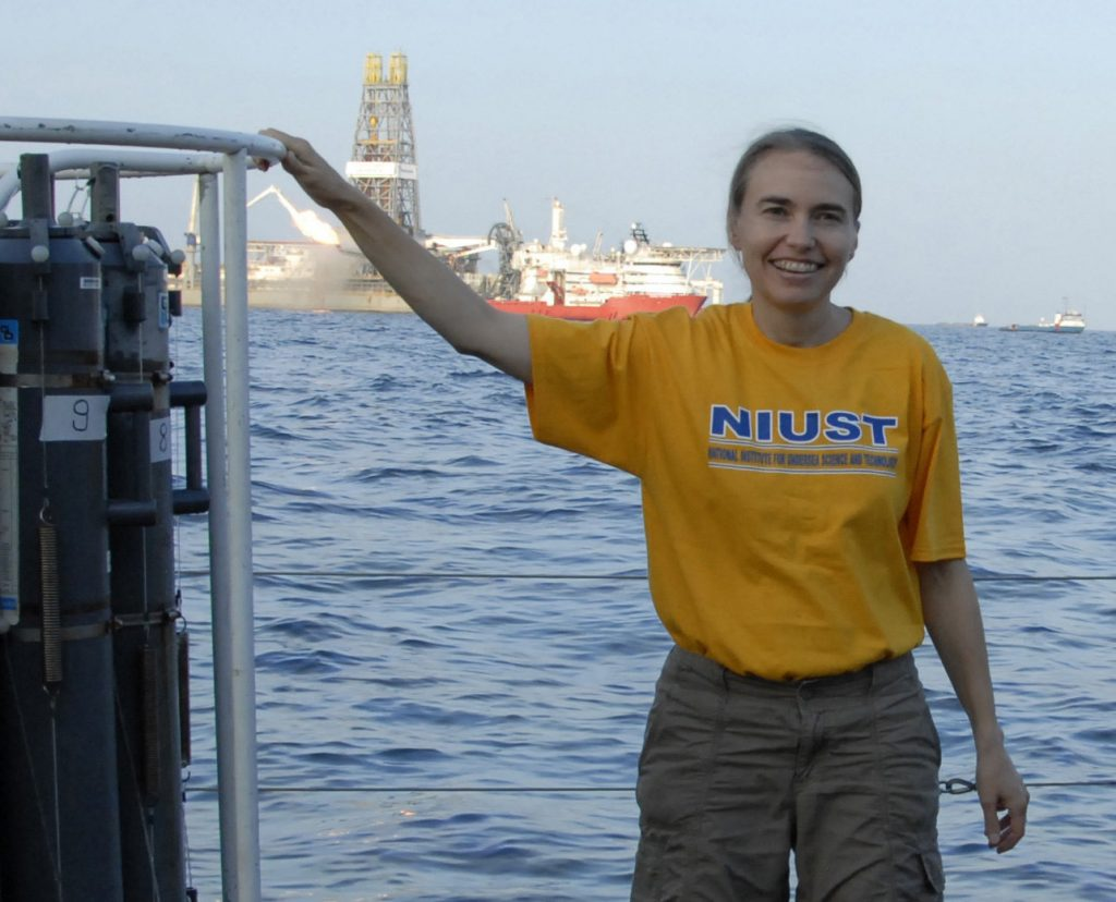 Dr. Samantha Joye's blog includes her early research experiences related to the oil-spill as shown here with her near the site of the Deepwater Horizon while efforts were underway to cap the spill (in the background).  (Photo credit: S. Joye)