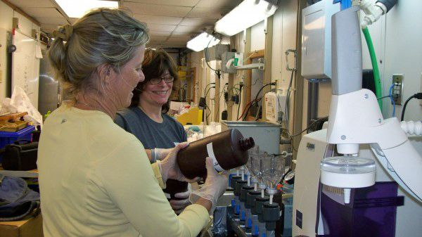 Teacher Mary St. Denis (R) filters water with Dr. Teresa Greely (L) at the lab onboard the R/V Weatherbird II.