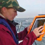 Ph.D. student Jena Brown (Naval Postgraduate School) follows the drifters' movement on her ipad as reported via their GPS devices. (Photo by Steve Layton with Gary Finch Outdoors)